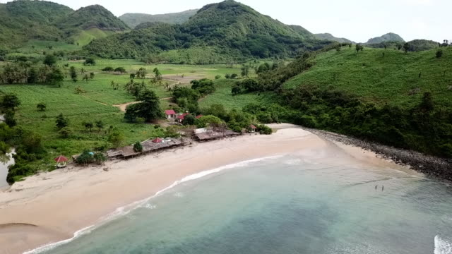 aerial: rising over lombok coastline to green landscape in lombok, bali - bali stock videos & royalty-free footage