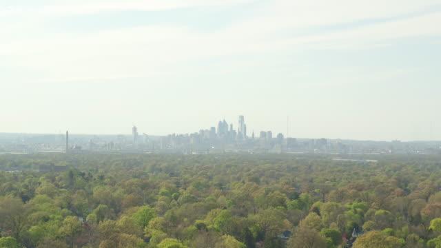 Aerial rising over trees toward Philadelphia skyline