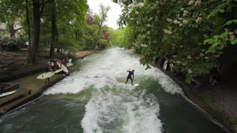 aerial river surfing, rough rapids, dismount at conclusion - munich, germany - rapids river stock videos & royalty-free footage