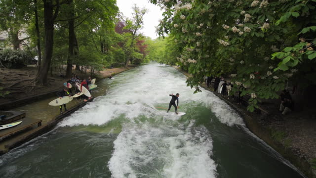 aerial river surfing, rough rapids, dismount at conclusion - munich, germany - ruscello video stock e b–roll