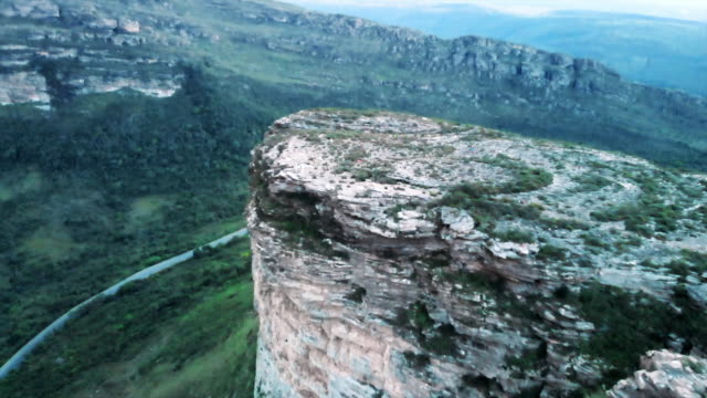 aerial: road in lush green valley under scenic plateau in chapada, brazil - rock type stock videos and b-roll footage