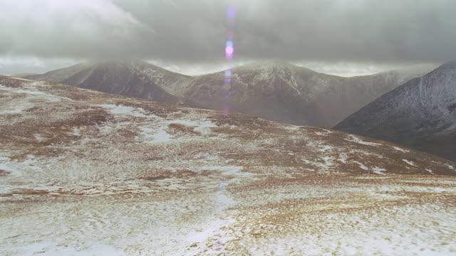 vidéos et rushes de aerial rocky green hills, some snow, scotland - écosse