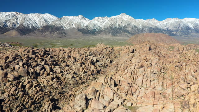 aerial: rocky hills and crevice before long green plains and tall snow capped mountains - alabama hills, california - crevice stock videos & royalty-free footage