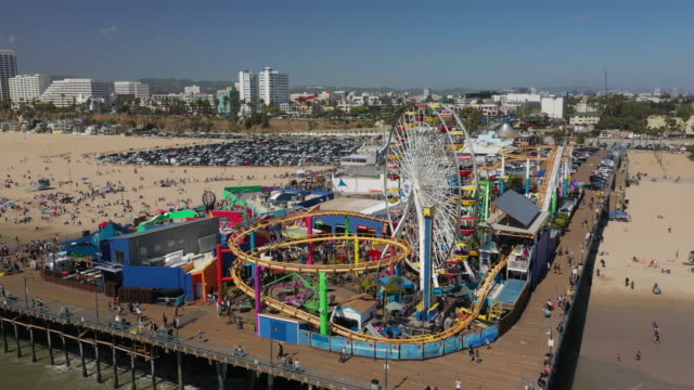 aerial: roller coasters and ferris wheel on santa monica pier with crowds of tourists - santa monica, california - santa monica pier stock videos & royalty-free footage