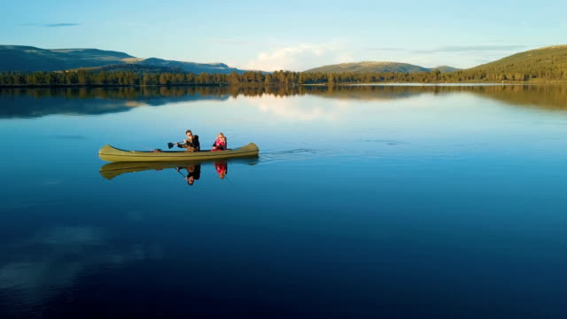 aerial / romantic canoeing in rondane national park, norway - kajakdisziplin stock-videos und b-roll-filmmaterial