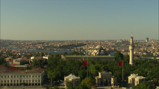 aerial rotate and zo from flags to reveal mosques in istanbul - turchia video stock e b–roll
