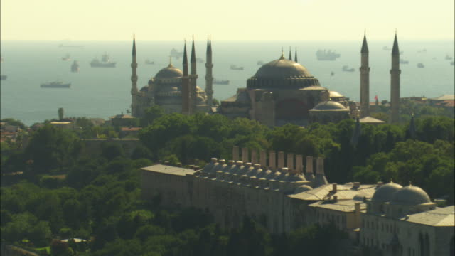 aerial rotate around suleymaniye and hagia sofia mosques with ships in background backlit - famous place stock videos & royalty-free footage
