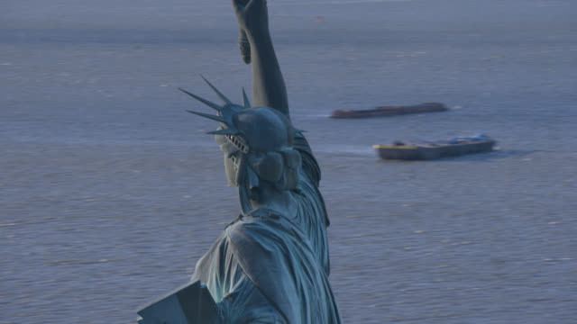 aerial rotating around statue of liberty in new york harbor. landmarks. cruise ship in bg.