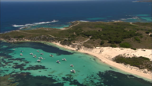 aerial rottnest island - coastline narrow sandy beaches and blue sea and reefs / motor cruise boats moored off shore / coastline road / lighthouse - indian ocean stock videos & royalty-free footage