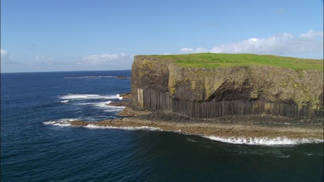 aerial rounding fingal's cave in basalt cliffs on coast of staffa / inner hebrides, scotland - basalt stock videos & royalty-free footage