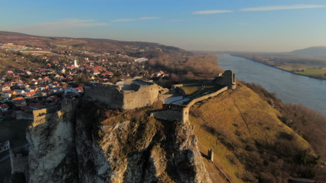 aerial: ruins of devin castle in bratislava, slovakia with town and river below - slovakia stock videos & royalty-free footage