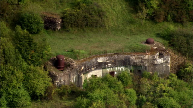 vídeos de stock e filmes b-roll de aerial ws ruins of wwii maginot line and entrance to ouvrage schoenenbourg / bas-rhin, france - linha maginot