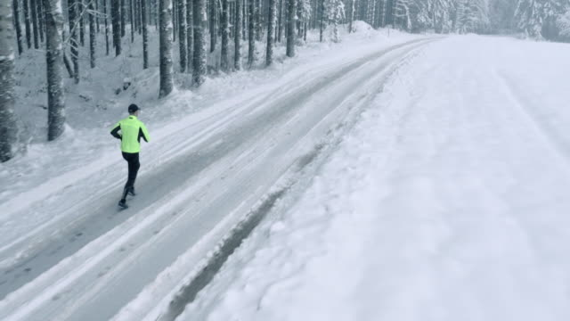 Aerial Runner running on snowy forest road