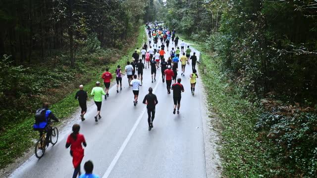 stockvideo's en b-roll-footage met luchtagenten die een marathon op weg door bos lopen - hardnekkigheid