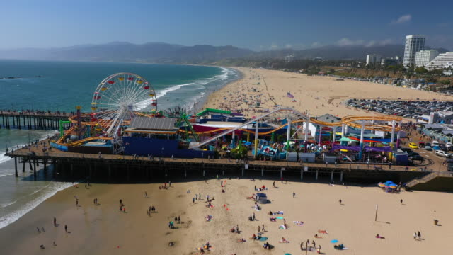 aerial: santa monica pier on a sunny day with crowded beach and mountains in the distance - santa monica, california - santa monica pier stock videos & royalty-free footage
