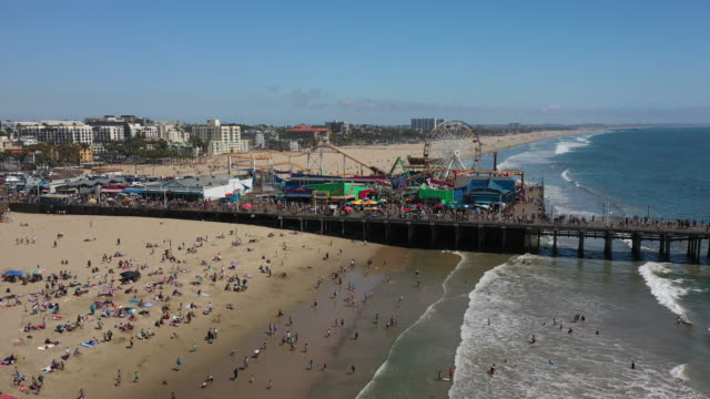 aerial: santa monica pier on a sunny day with crowded beach  - santa monica, california - santa monica pier stock videos & royalty-free footage