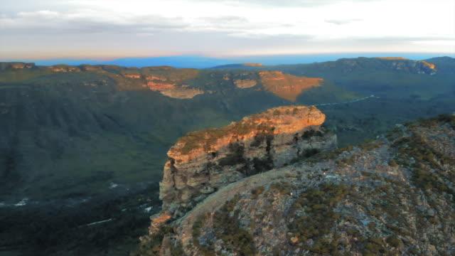 aerial: scenic plateau over lush green valley in chapada, brazil - altopiano video stock e b–roll