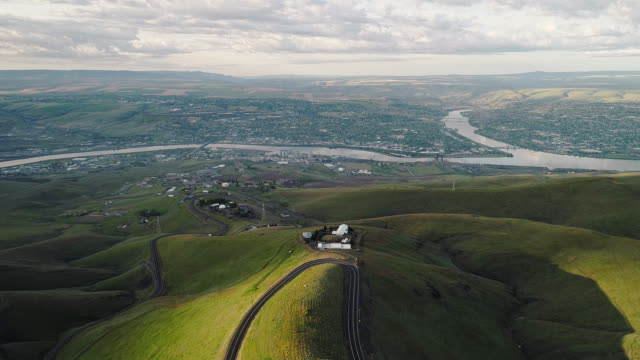 aerial scenic view to the hills and the historic old spiral highway toward two neighbor towns, lewiston, idaho, and clarkston, washington, at the states' border. early sunny morning at springtime. drone video footage with the backward camera motion. - idaho stock videos & royalty-free footage