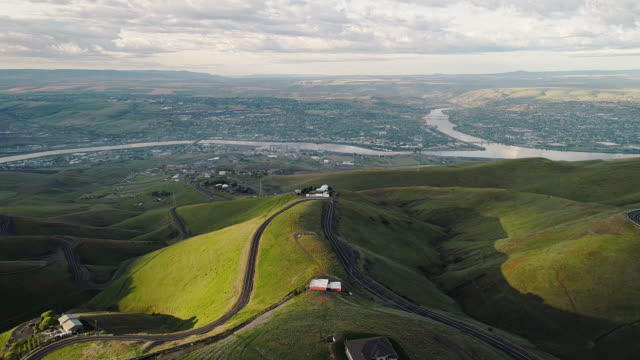aerial scenic view to the hills and the historic old spiral highway toward two neighbor towns, lewiston, idaho, and clarkston, washington, at the states' border. early sunny morning at springtime. drone video footage with the backward camera motion. - pasture stock videos & royalty-free footage