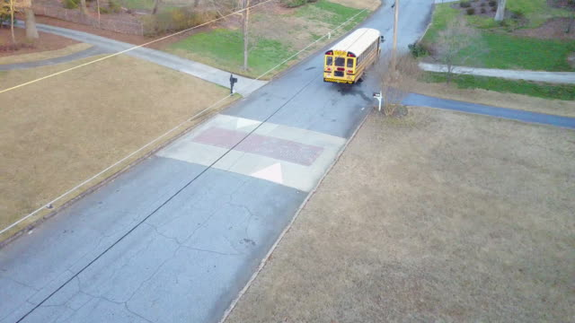 aerial, school bus drives through suburbs - south stock videos & royalty-free footage