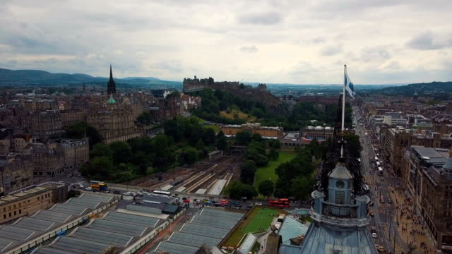 vidéos et rushes de aerial /scotland flag blowing in the wind with edinburgh skyline cityscape - écosse