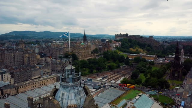 aerial /scotland flag blowing in the wind with edinburgh skyline cityscape - scotland stock videos & royalty-free footage