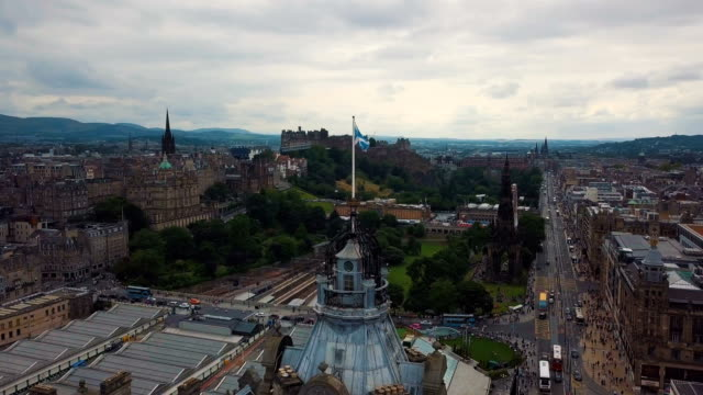 aerial /scotland flag blowing in the wind with edinburgh skyline cityscape - edinburgh scotland stock videos & royalty-free footage