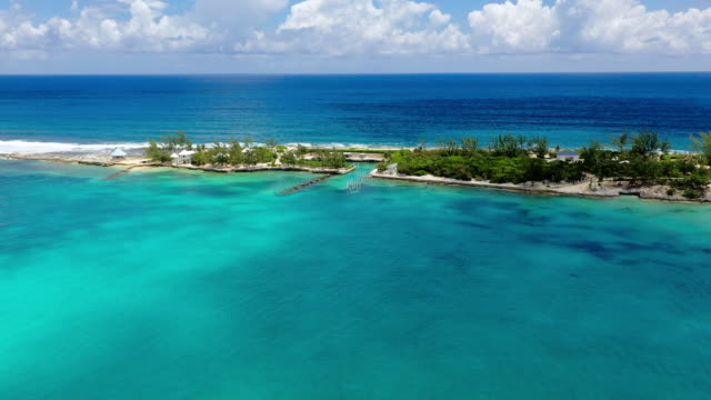 aerial: secluded homes on narrow peninsula surrounded by gorgeous tropical water - nassau, bahamas - caribbean stock videos & royalty-free footage