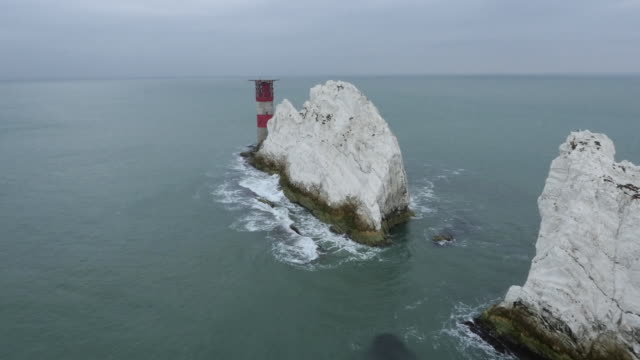 Aerial sequence running alongside the dramatic Needles chalk stack and Needles Lighthouse, Isle of Wight, UK.