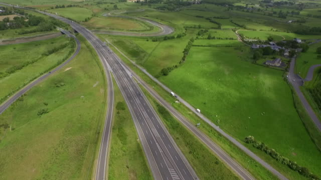 Aerial sequence showing the M18 motorway cutting through green fields in County Clare in the Republic of Ireland.