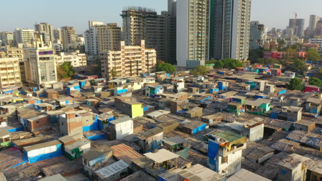 aerial: shanties in crowded slum against modern residential skyscrapers - mumbai, india - slum stock videos & royalty-free footage