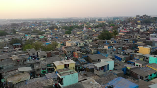 aerial: shanties in crowded slum against sky during sunset - mumbai, india - slum stock-videos und b-roll-filmmaterial