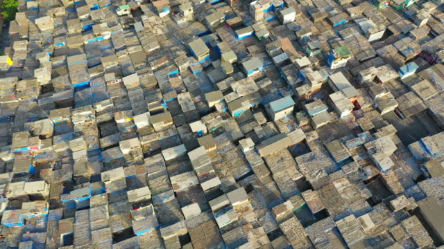 aerial: shanties in crowded slum by modern skyscrapers against sky - mumbai, india - slum stock-videos und b-roll-filmmaterial