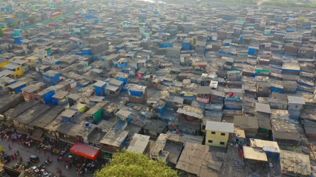 aerial: shanties in slum by sea during sunset - mumbai, india - povertà video stock e b–roll