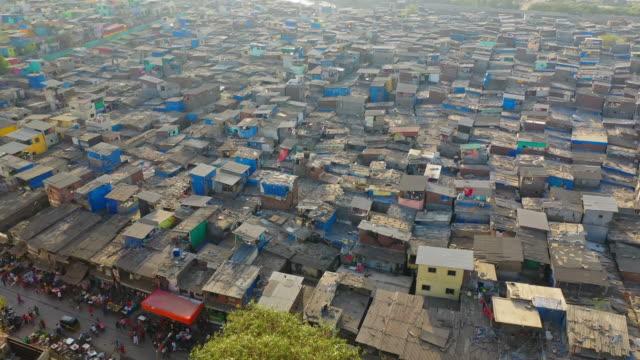 aerial: shanties in slum by sea during sunset - mumbai, india - poverty stock videos & royalty-free footage