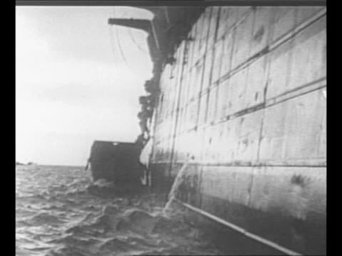 Aerial ship surrounded by landing crafts / montage assault troops climb down nets on side of ship to get into landing craft / montage German soldier...