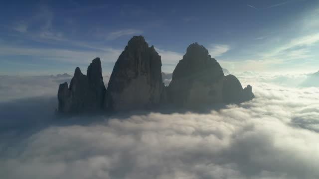 aerial shot above the clouds flying towards tre cime di lavaredo, dolomites, italy - tre cimo di lavaredo stock videos & royalty-free footage