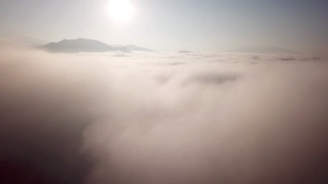 aerial shot above the clouds sunrise time in to the mist on the sky - atmospheric mood stock videos & royalty-free footage