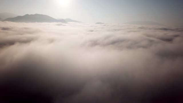 aerial shot above the clouds sunrise time in to the mist on the sky - stratosphere stock videos & royalty-free footage