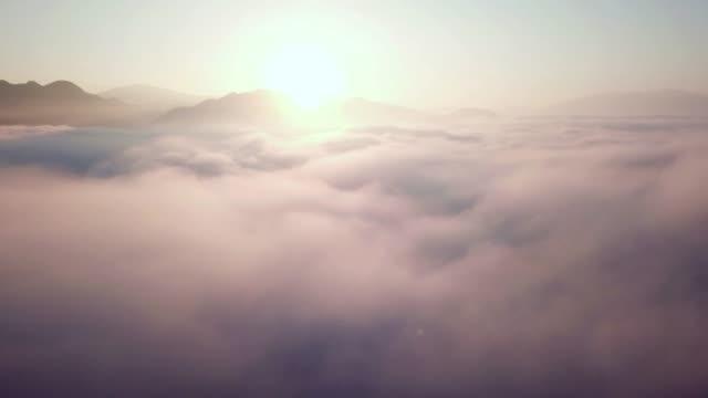 vídeos de stock, filmes e b-roll de tiro aéreo acima das nuvens com nascer do sol e céu azul - acima