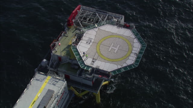 Aerial shot around a wind farm rig off the coast of Denmark.