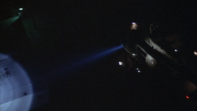 aerial shot as a police helicopter shines a spotlight on the ground. - hubschrauber stock-videos und b-roll-filmmaterial