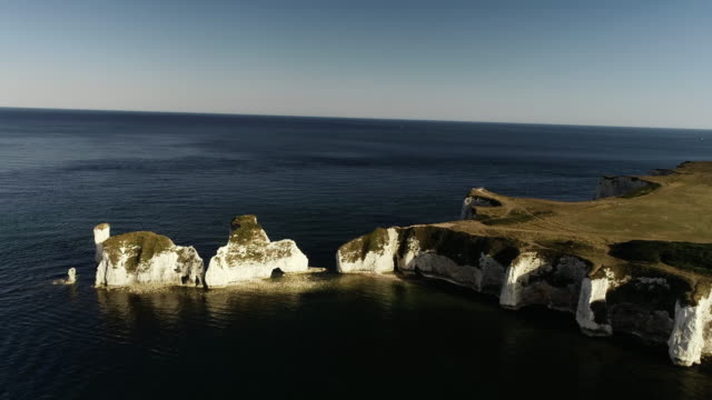aerial shot at sunset moving towards old harry rocks, dorset, england, united kingdom - rock face stock videos & royalty-free footage