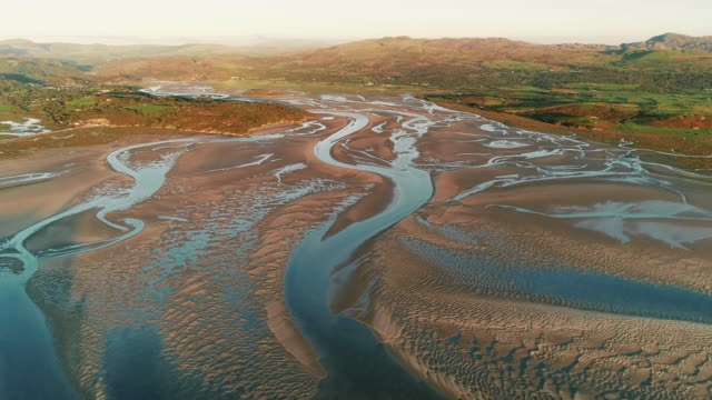 aerial shot at sunset showing low tide in an estuary, borth-y-gest, wales, united kingdom - low tide stock videos & royalty-free footage