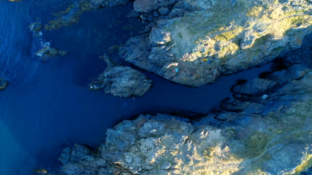 aerial shot bird eye view of a drone descending over group of people standing on cliffs in the sea - roccia video stock e b–roll