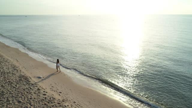 vidéos et rushes de tir aérien par drone, jeune femme promenades près de la plage. - lagon