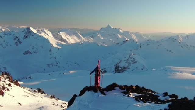 aerial shot circling a skier standing on the edge of a mountain looking into the distance - snowcapped mountain stock videos & royalty-free footage