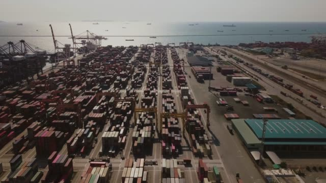 aerial shot circling over container yard with loaded cargo ship in dock - market retail space stock videos & royalty-free footage