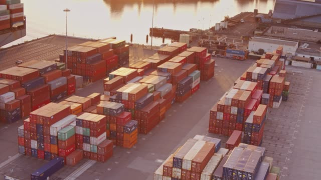 stockvideo's en b-roll-footage met luchtfoto shot cirkelen over container yard met geladen vrachtschip in dock - haven