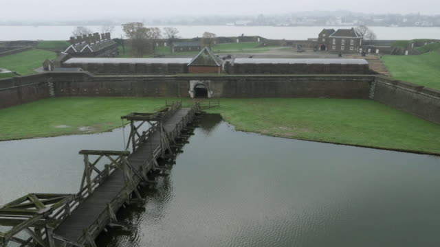 vídeos de stock, filmes e b-roll de aerial shot descending to reveal a ground level view across tilbury fort's drawbridge, east london, uk. - drawbridge